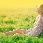 A woman relaxing in a green field, representing a spring clean meditation