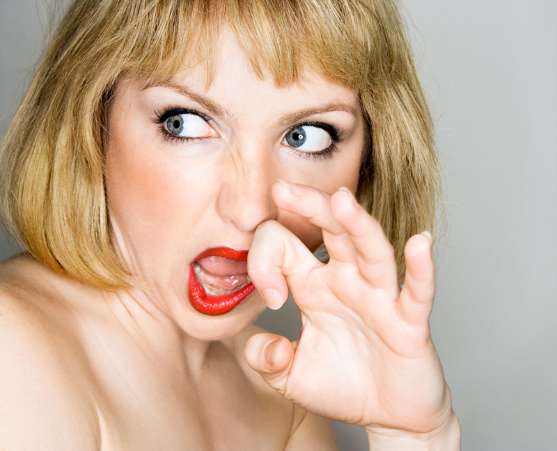 Woman with a disgust expression pushing her nose to one side.